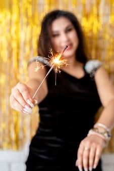 Geburtstagsparty. schöne junge frau, die wunderkerze und ballon auf goldenem hintergrund hält