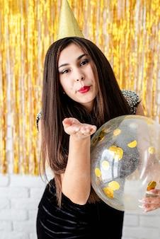 Geburtstagsparty. schöne junge frau im partykleid und im geburtstagshut, die ballon auf goldenem hintergrund halten