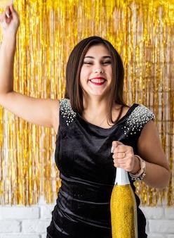 Geburtstagsparty. schöne lächelnde brünette frau im schwarzen partykleid, das ihren geburtstag hält ballon feiert