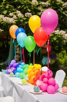Geburtstagstabelle mit regenbogenballonen. sommerurlaub im park.