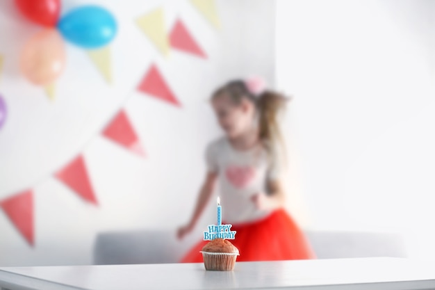 Geburtstagstorte auf weißem tisch mit kleinem mädchen auf hintergrund