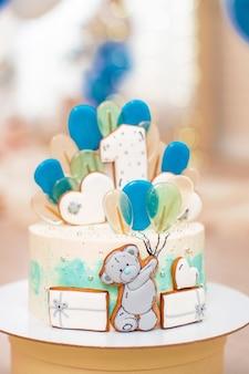 Geburtstagstorte für 1 jahr mit luftballons lebkuchenbär mit zuckerguss verziert.