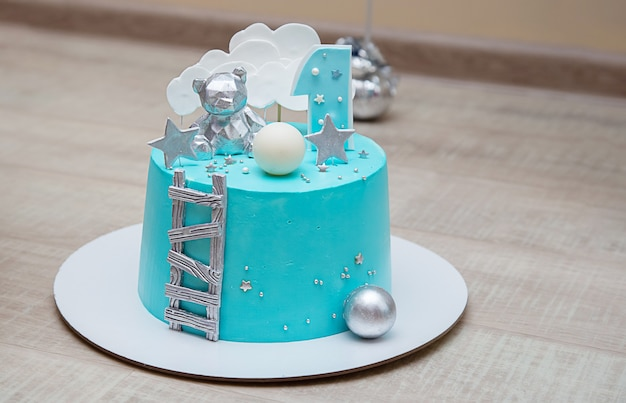 Geburtstagstorte für einen kleinen jungen mit hellblauer spiegelglasur. schokoladendekor und nummer eins.