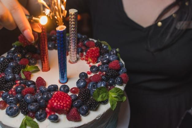 Geburtstagstorte mit kerzen. kerzen auf kuchen. kuchen für den urlaub. schöner weißer kuchen mit erdbeeren auf dunklem hintergrund. vertikales foto.