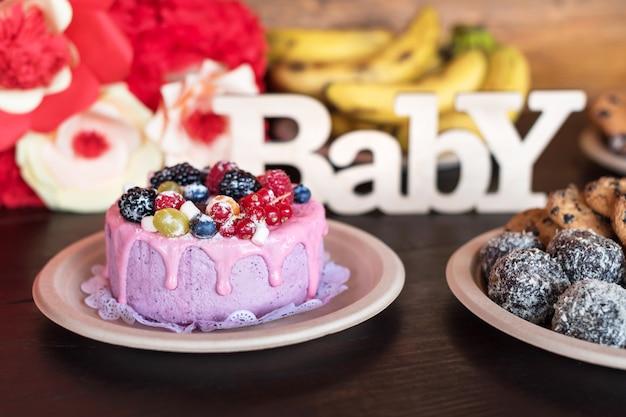 Geburtstagstorte und muffins mit hölzernem grußzeichen auf dunklem tisch. holz singen mit buchstaben baby und feiertagsbonbons.