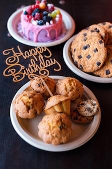 Geburtstagstorte und muffins mit hölzernem grußzeichen auf rustikaler wand. holz singen mit buchstaben alles gute zum geburtstag und feiertagsbonbons.
