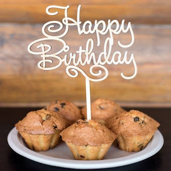 Geburtstagstorten und muffins mit hölzernem grußzeichen auf rustikaler wand. holz singen mit buchstaben alles gute zum geburtstag und feiertagsbonbons.