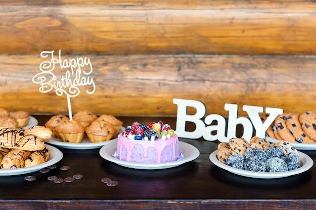 Geburtstagstorten und muffins mit hölzernen grußzeichen auf rustikaler wand. holz singen mit buchstaben alles gute zum geburtstag, baby und feiertagsbonbons.