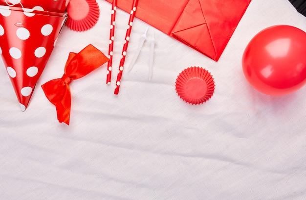 Geburtstagswohnung, draufsicht und kopierraum für text, rahmen oder hintergrund mit roten festivalgegenständen, partyhüten und luftschlangen, geburtstags- oder partygrußkarte