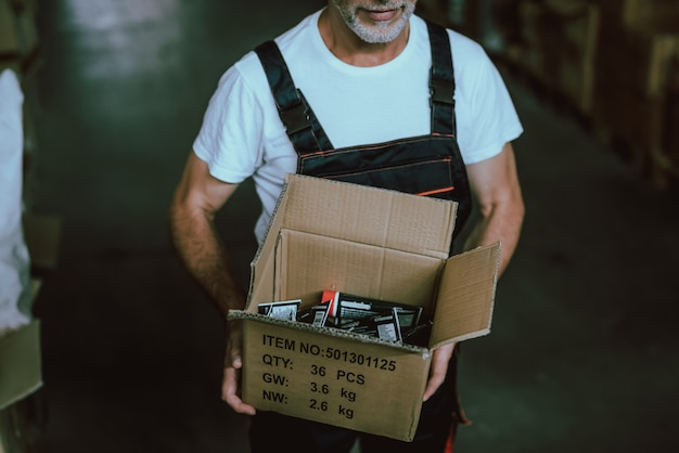 Ged mann in uniform mit pappkarton