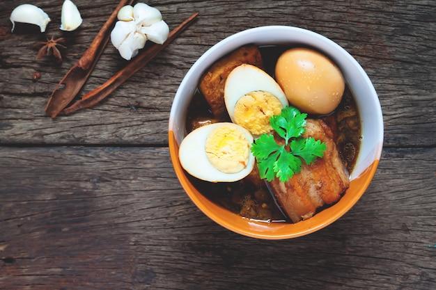 Gedämpfte eier und schweinefleisch oder eier und schweinefleisch in der braunen soße in der schüssel mit gewürzen auf holztisch