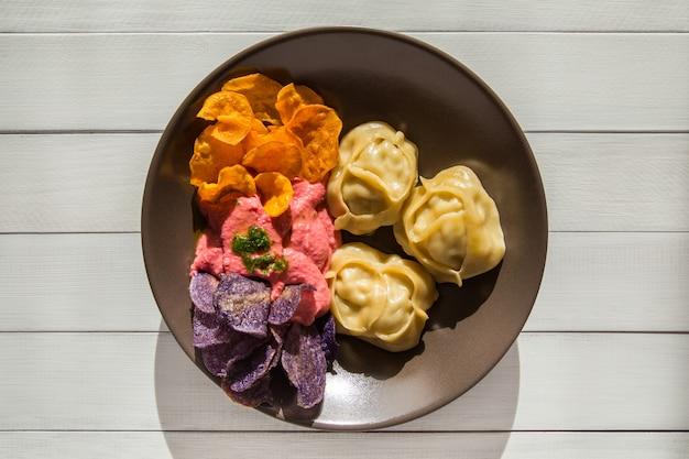 Gedämpfte fleischknödel manti mit rote-bete-hummus und farbigen pommes frites von lila kartoffeln und süßkartoffelchips