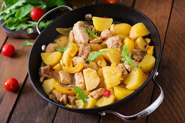 Gedämpfte kartoffeln mit fleisch und gemüse in einer bratform auf einem holztisch