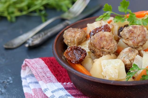Gedämpfte kartoffeln mit fleischbällchen, karotten und sonnengetrockneten tomaten in einer schüssel