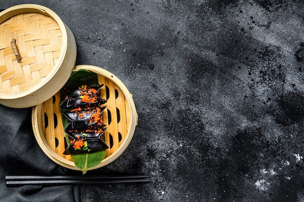 Gedämpfte knödel dim sum im bambusdampfer. schwarzer hintergrund. draufsicht. speicherplatz kopieren