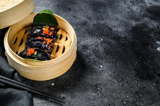 Gedämpfte knödel dim sum im bambusdampfer. schwarzer hintergrund