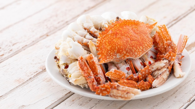 Gedämpfte krabben in weißer keramikplatte auf weißem altem holzstrukturhintergrund mit kopienraum für text, blaue schwimmkrabbe, blumenkrabbe, blaue krabbe
