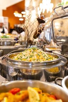 Gedämpfter reis mit mais und frühlingszwiebeln in einem topf.