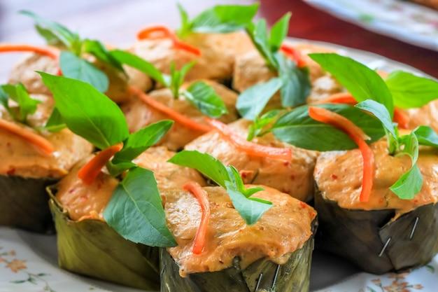 Gedämpfter thai-curryfisch in bananenblattbechern mit basilikumblattdekor, (hor mok pla)