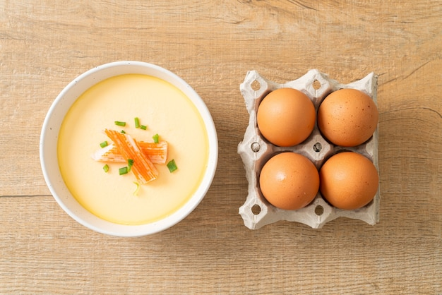 Gedämpftes ei mit krabbenstange und frühlingszwiebeln