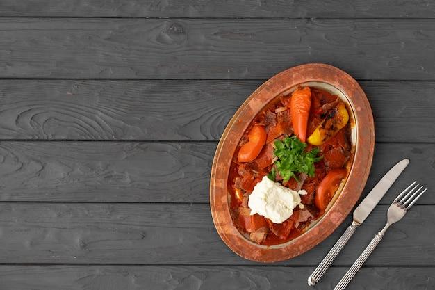 Gedämpftes fleisch mit gemüse in tomatensauce auf holzoberfläche