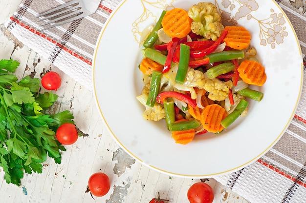 Gedämpftes gemüse - blumenkohl, grüne bohnen, karotten und zwiebeln