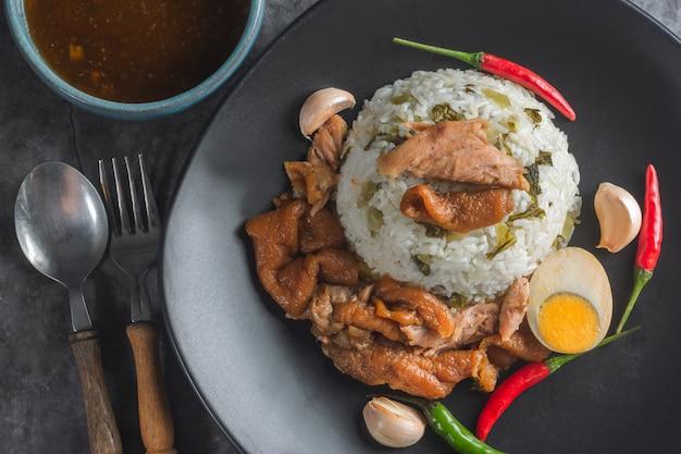 Gedämpftes schweinefleischbein auf reis mit soßen-thailändischem rezept.
