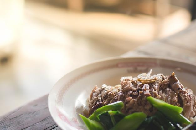 Gedämpftes schweinefleischbein mit reis auf dem holztisch, thailändisches lebensmittel