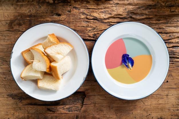 Gedämpftes toastbrot mit buntem vanillepudding auf holzhintergrund