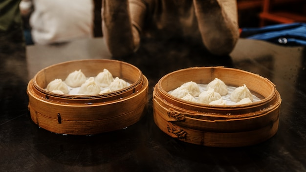 Gedämpftes xiao long bao (suppenknödel) im bambuskorb. serviert im restaurant in taipeh, taiwan.
