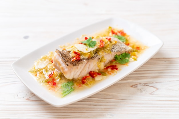 Gedämpftes zackenbarsch-fischfilet mit chili-limetten-sauce in limetten-dressing