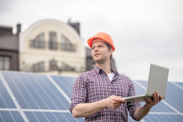 Gedanken, idee. mann in schutzhelm mit offenem laptop, der nachdenklich zur seite steht, die vor dem hintergrund der solarbatterie in der nähe des neuen hauses steht