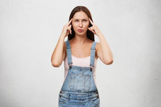 Gedanken, konzentration und fokuskonzept. bild der lustigen jungen kaukasischen frau in den stilvollen kleidern, die konzentrierten blick haben