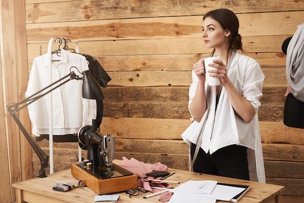 Gedanken tragen mich weg. junger niedlicher kleidungsdesigner, der in der werkstatt steht, pause vom nähen hat, kaffee trinkt und denkt, während er beiseite schaut und neues design des kleidungsstücks plant