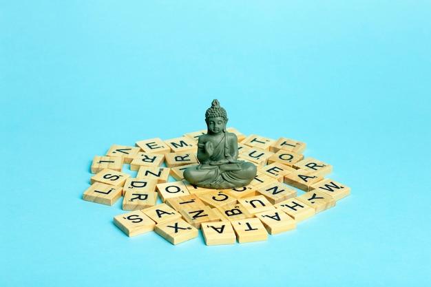 Gedankenkonzept. eine meditierende figur sitzt auf einem stapel verschiedener buchstaben. das konzept von denken, verstand, entwicklung und kreativität