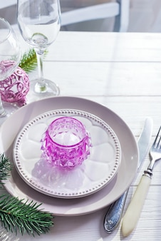 Gedeck für weihnachtsweiße tabelle mit purpurroten dekorelementen mit grünem niederlassungs-weihnachtsbaum