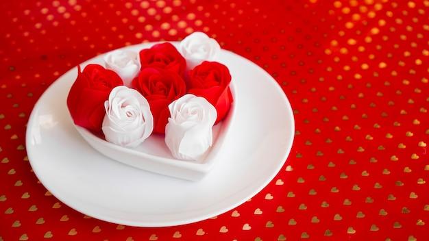 Gedeck in rot und weiß - für valentinstag oder andere veranstaltung. weißer teller in form eines herzens mit einem rosendekor auf einem roten