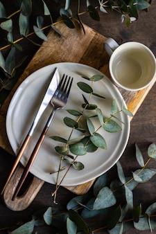 Gedeck mit frischen eukalyptusblättern auf holztisch
