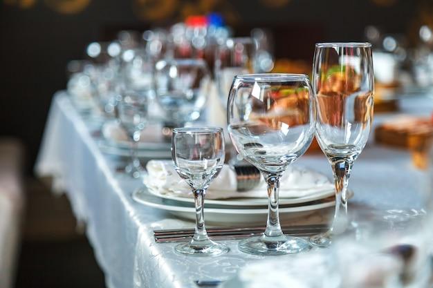 Gedeck mit gläsern, tellern, servietten und lebensmittel