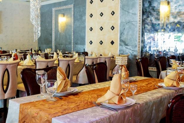 Gedeckter service des verpflegungstisches mit tafelsilber- und stielglasrestaurant vor partei