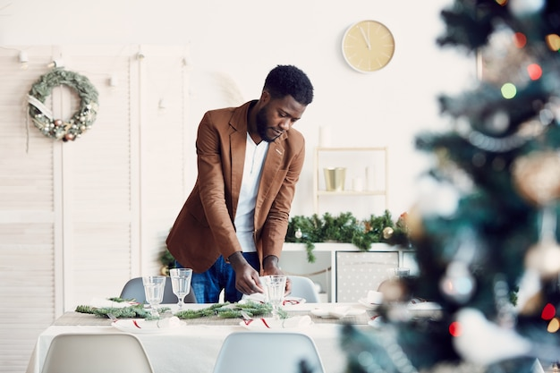 Gedeckter tisch des jungen afrikanischen mannes für weihnachtsfeier