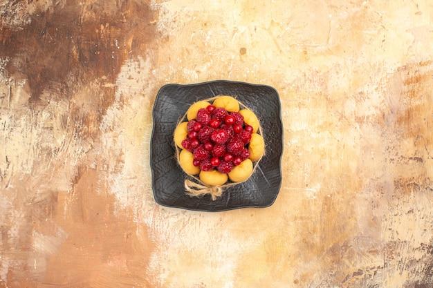 Gedeckter tisch für kaffee- und teezeit mit himbeeren auf kuchen auf gemischtem farbtisch
