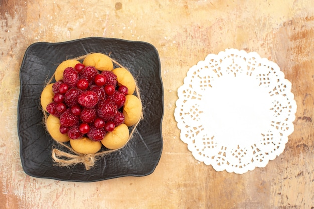 Gedeckter tisch für kaffee- und teezeit mit himbeeren auf kuchen und serviette auf gemischtem farbtisch