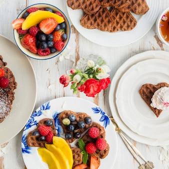 Gedeckter tisch zum frühstück mit hausgemachten schokoladenwaffeln und berr