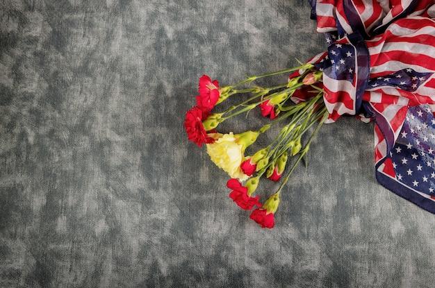 Gedenken sie rosa nelkenblumen für gedenkfeiertag mit amerikanischer flagge