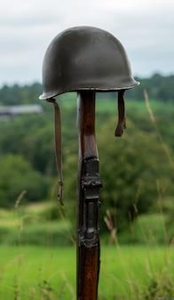 Gedenkkreuz auf dem schlachtfeld mit dem symbol eines gefallenen m1-gewehrs eines us-soldaten mit helm