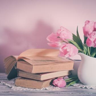 Gedichtstillleben mit büchern und rosa tulpen