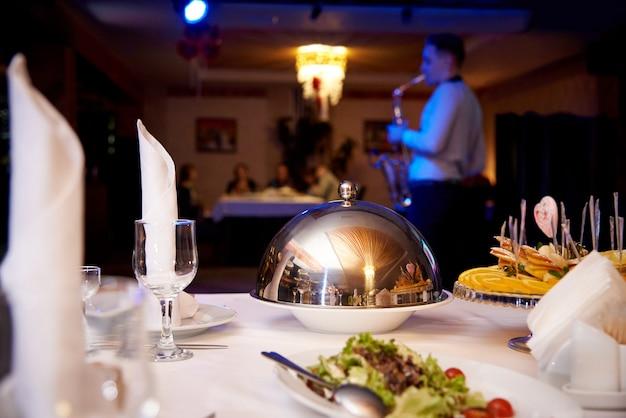 Gedienter abendtisch heißer teller auf dem haubenbehälter auf dem servertisch auf einem unscharfen hintergrund, der saxophonisten für gäste spielt.