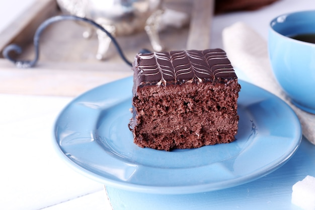 Gedienter tisch mit einer tasse tee und schokoladenkuchen auf blauen platten nahaufnahme close