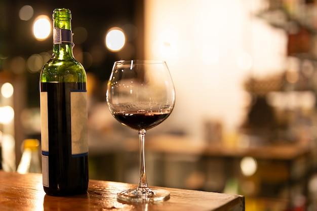 Gedreht in schwachem licht und hoher iso-flasche und glas rotwein auf holzspitze.